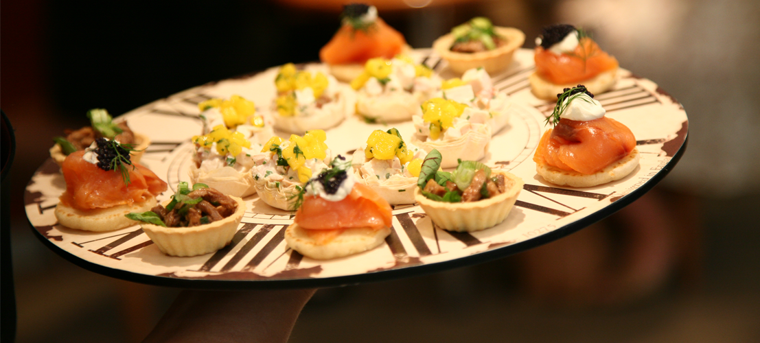 Canapés on a clock-themed platter at a corporate event.