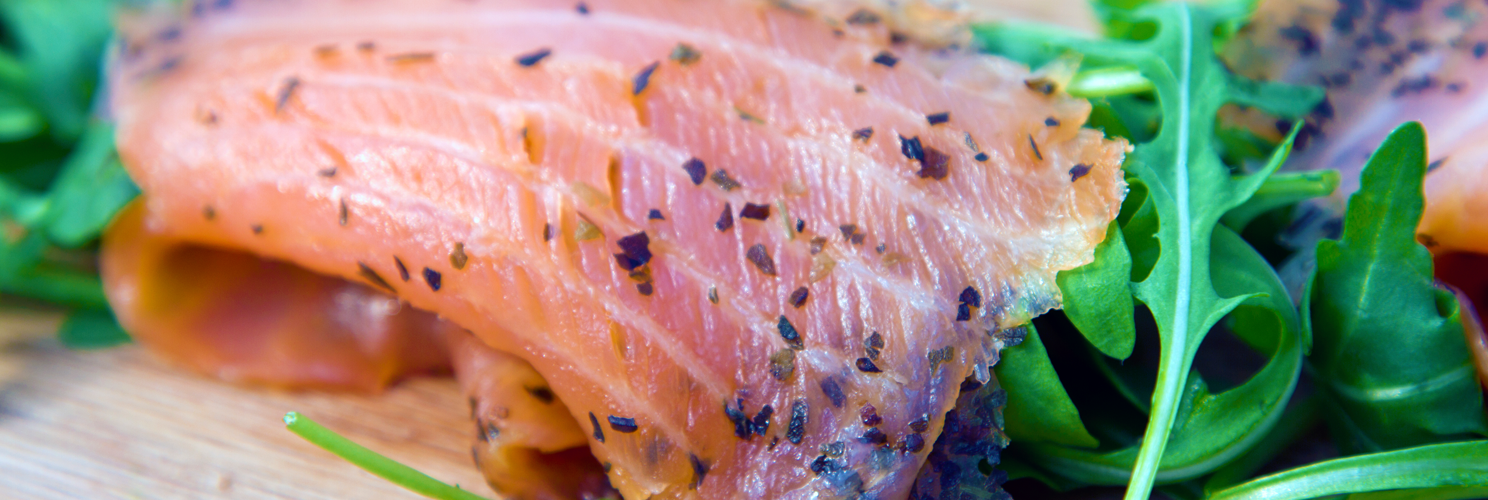 Fresh smoked salmon with rocket on a wooden chopping board.