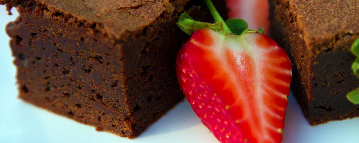 Image of chocolate brownies served with fresh strawberries.